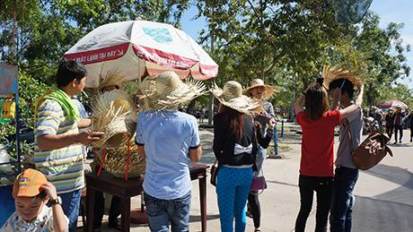 Du khách mua nón lá để chống lại nắng nóng
