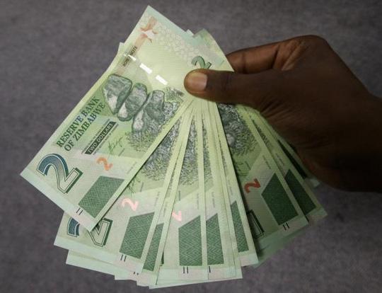 Một người đàn ông Zimbabwe với số tiền trái phiếu rút được hôm 28-11 ở thủ đô Harare. Ảnh: REUTERS